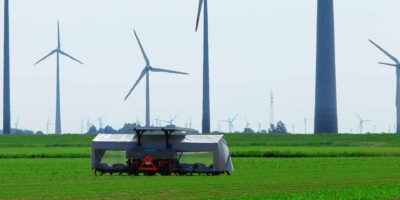Agriculture - solar powered weeding machine in the fields, with wind turbines in the background