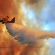firefighting aircraft dropping water over a forest fire
