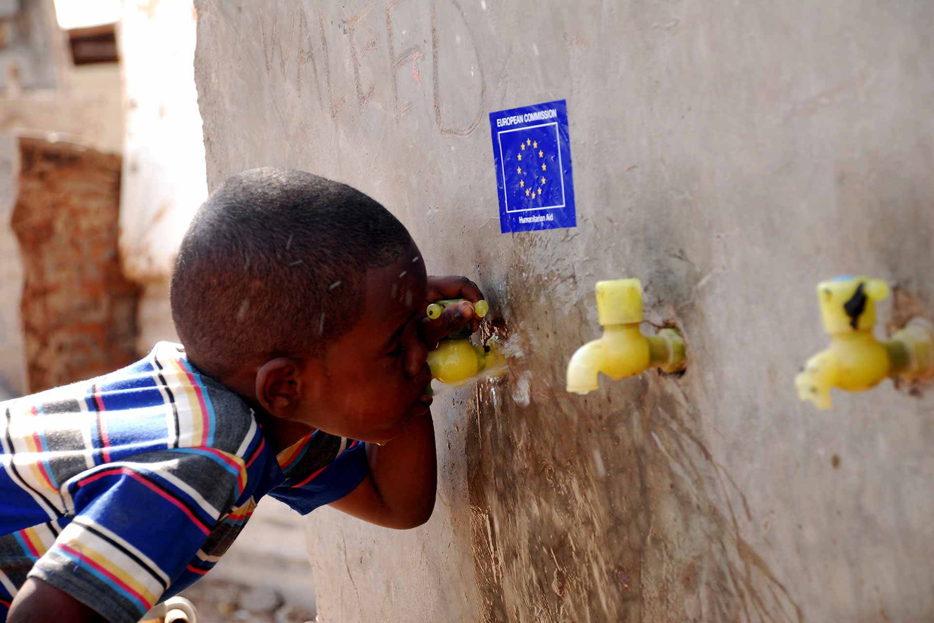 A young Somali refugee drinks water from a public tap provided by EC Humanitarian Aid