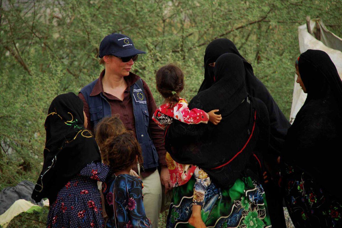 An EU official, centre left, listens to Yemeni refugees