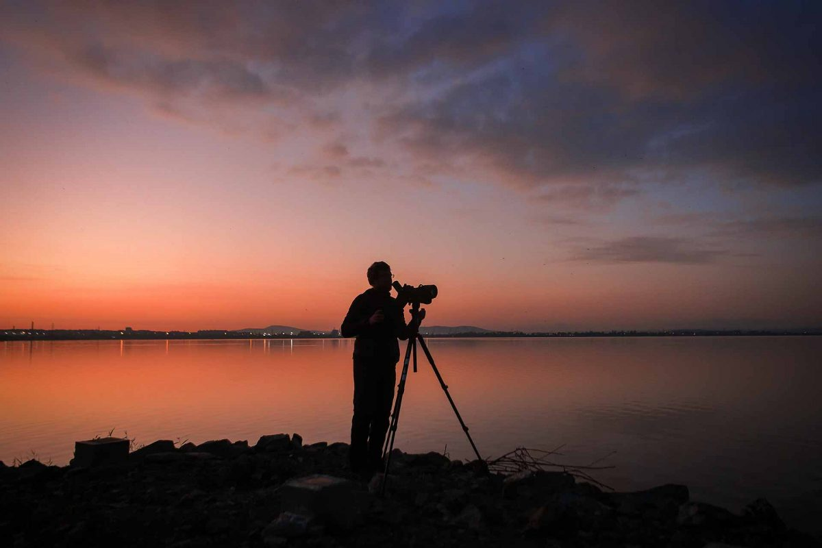 An ornithologist watching birds at Lake Burgas before sunrise